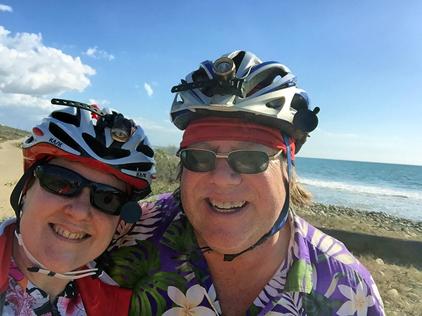Laurie and Mark at the ocean wearing bike helmuts