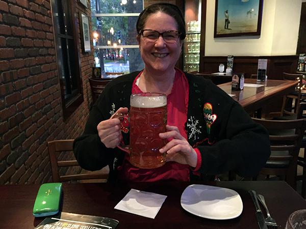 Laurie holding a monster size beer while wearing a holiday sweater
