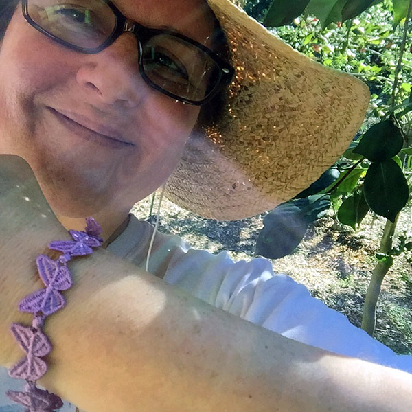 Laurie shows off a purple butterfly bracelet in the camellia forest