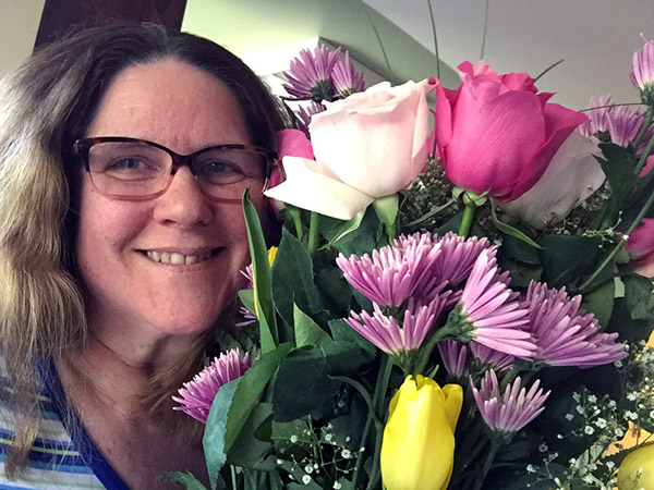 Laurie holding a bouquet of roses, tulips, mums and other flowers in pink, purple and yellow.