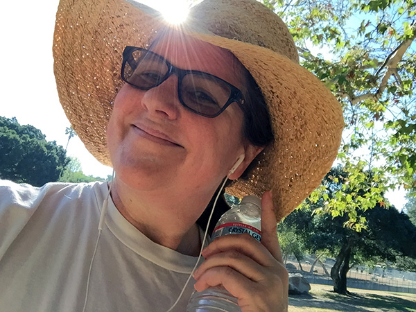 Laurie in her straw hat in a ray of sunshine holding a bottle of water at the park.