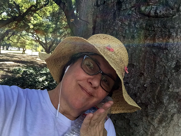 Laurie next to a tree with a rainbow encircling her at the hatline
