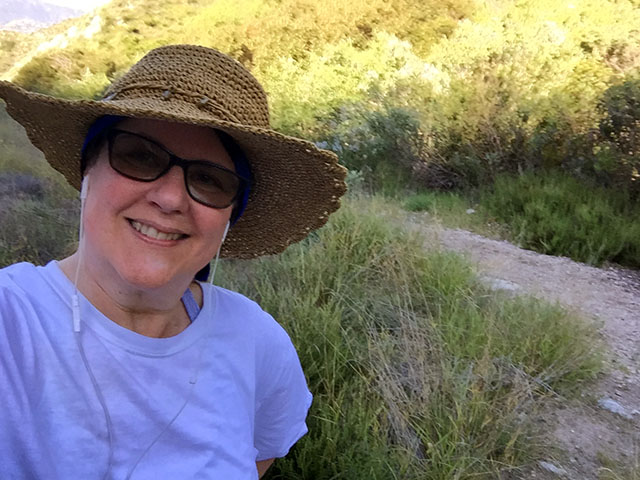 Laurie smiling in her straw hat with the sun shining down on the hiking trail.