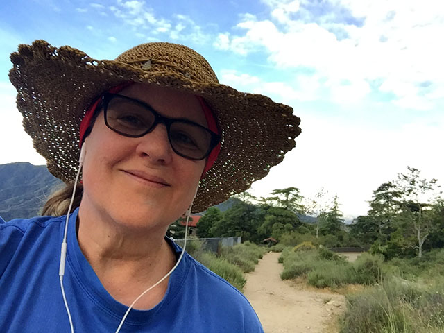 Laurie in her big straw hat at the base of the hiking trail