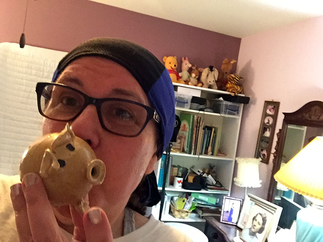 Laurie playing a ceramic whistle that is shaped like a pig