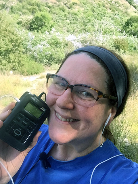Laurie holds up her Roland Recorder and smiles into the camera while hiking
