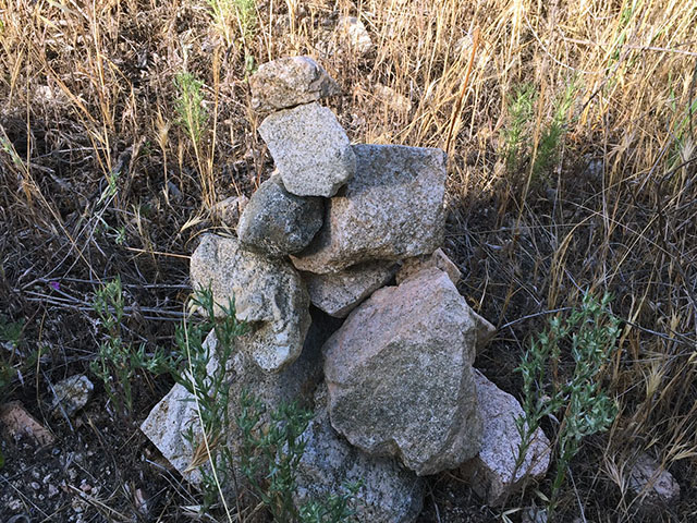 Prayer rocks along the trail stacked in a loose pyramid configuration supporting a top rock