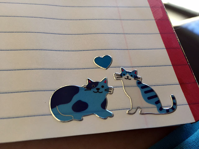 Two blue cat stickers with a floating blue heart smile up from the lower corner of one journal page