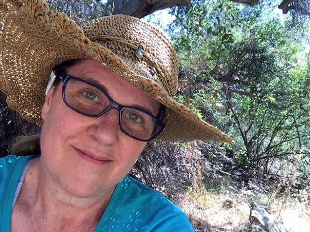 Laurie gives an emotional smile in close-up under the trees