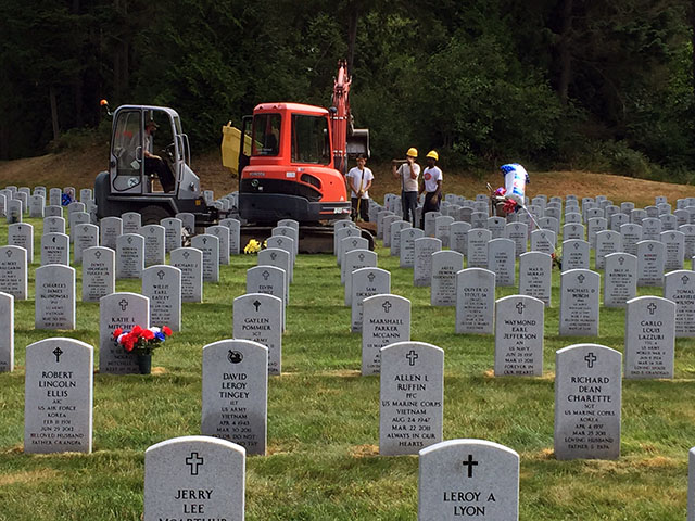 Rows of headstones with the grave digging backhoe behind
