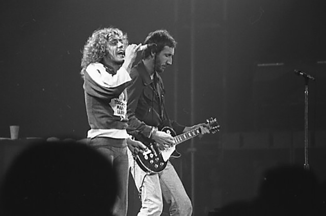 Black and white photo of Roger Daltrey singing and Pete Townshend on guitar.