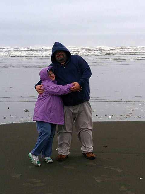 BCs Dave and Kathleen hug before the waves at the ocean on a typical grey Washington day