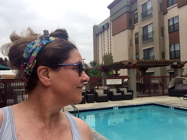 Laurie with hair up contemplates the hotel pool.