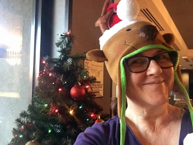 Laurie in front of a Christmas tree wearing a hat shaped like a reindeer