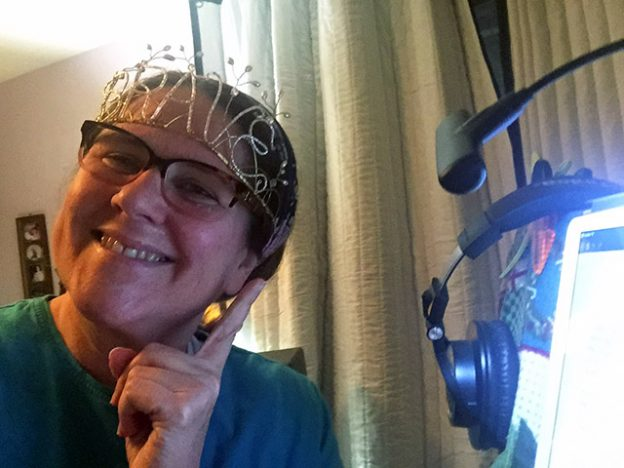 Laurie wearing a tiara that spells out the word BRAVE while smiling before her studio mic.