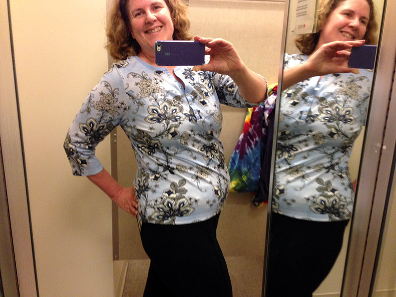 Laurie in the dressing room wearing slacks and printed top