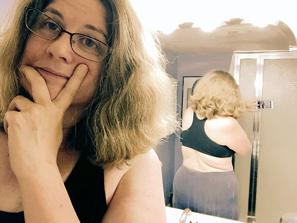 Laurie in sports bra and yoga pants in the mirror