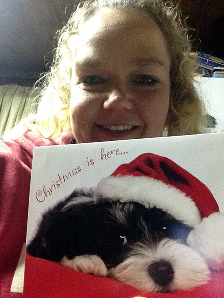Dawny holds a photo of a cute black and white puppy in a santa hat