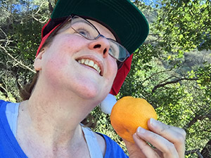 Laurie wears a santa hat and is looking up holding an orange on the hiking trail