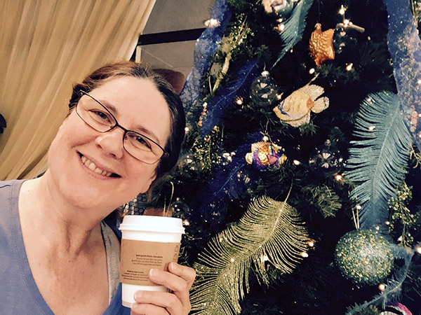 Laurie with coffee by Christmas tree
