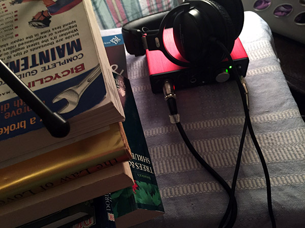 Focusrite Solo Audio Interface box with headphones on it next to a pile of books with Laurie's mic perched on top