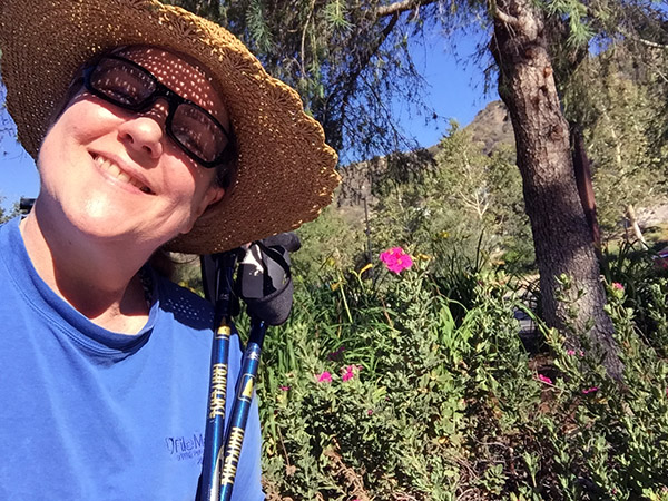 Laurie in a straw hat in front of some tall pink flowers at the trail head. Cloudless blue skies behind