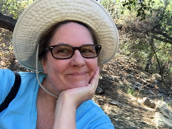 Laurie in glasses smiling with hat brim turned up