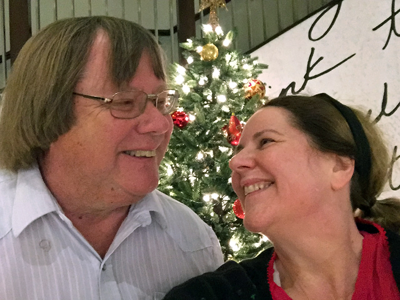Laurie and Mark make goo goo eyes in front of a Christmas Tree