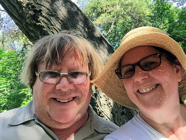 Laurie and Mark smiling under a tree