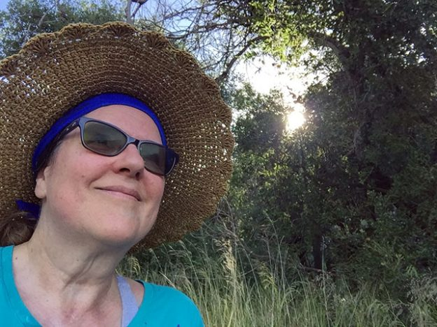 Laurie in a big straw hat sits under the trees and the sun light cascades down through the leaves.