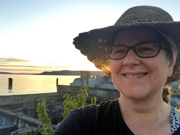 Laurie in her straw hat with the Puget Sound in the background at daybreak