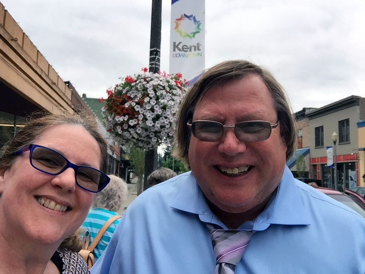 Laurie and Mark smiling in front of a banner that says Kent Downtown