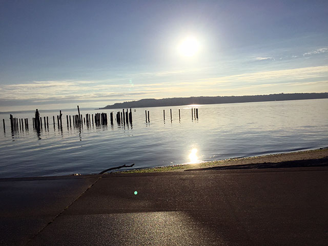 Sun across the water with pilings and still blueness