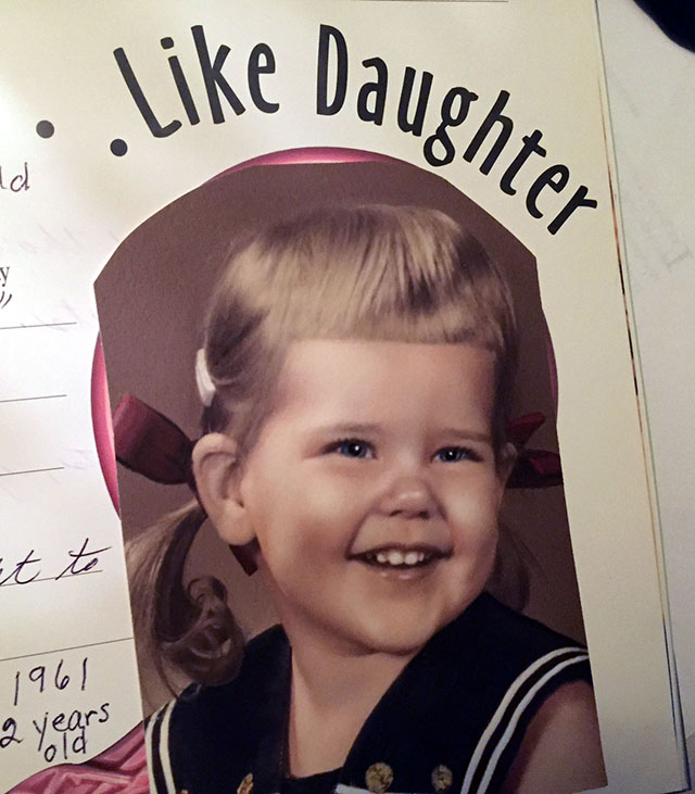 Laurie at two in pony tails with red ribbons in a sailer dress
