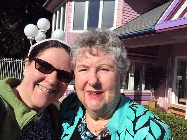 Laurie and her Mom outside a pink tea shop building on a sunny day