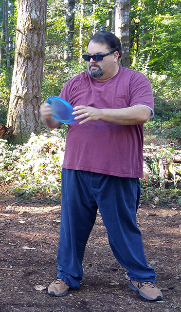 BC Dave holds a blue disc by some woods - ready to shoot