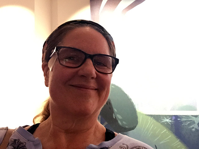 Laurie smiles in front of a mural inside Disney Animation's lobby