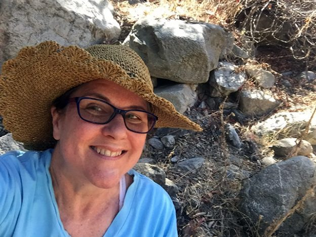 Very happy Laurie in her big straw hat grinning life a fiend on the podcast rock.