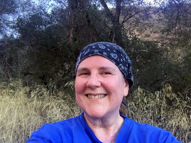 Laurie in black headscarf smiling on the mountain
