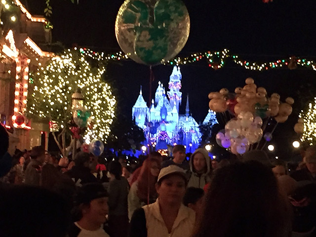 Glowing castle at Disneyland behind the crowd at night