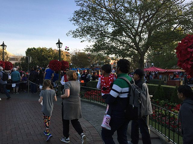 Families hurry to catch the parade at Disneyland