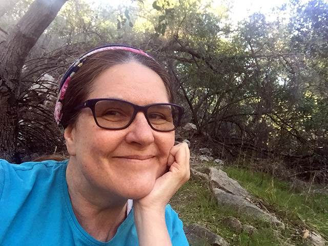 Laurie smiling under the tree at the podcast rock - hatless, wearing a mulit-colored headband and glasses.