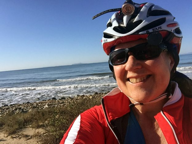 Laurie in bike gear in front of the gentle swells of the ocean.