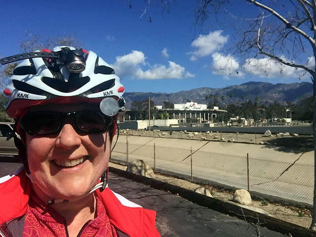 Laurie in bike gear in front of the Rose Bowl stadium on a sunny day with blue skies and puffy clouds