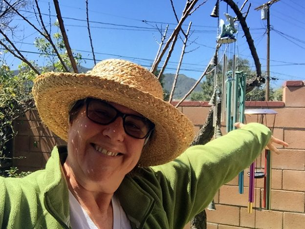 Laurie in a straw hat gestures on a sunny day in front of a set of colorful wind chimes hanging from a gnarled branch in front of a brick wall.