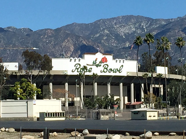 Font of the Pasadena Rose Bowl - features a rose about its name. Rolling foothills behind.