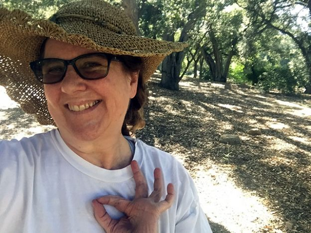 Laurie grins as she makes an OK sign down at the park on a sunny day. Trees in the background.