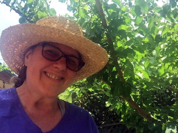 Laurie smiling near a tree in full leaf. She's wearing a straw fedora and a great big smile to compliment her lilac colored t-shirt.