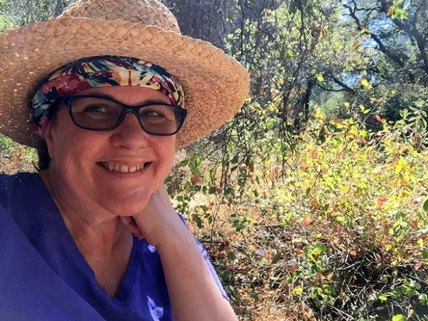 Laurie in a straw hat with a colorful bandana around her forehead smiles in front of a dried landscape of trees and wilted brush.