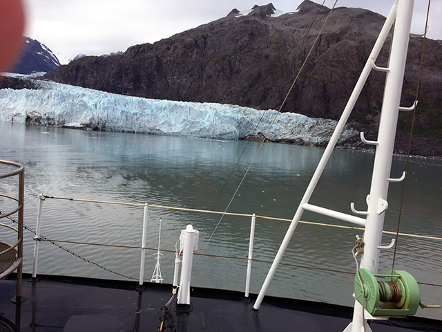 Icy blue-white glaciers flow into the grey calm bay waters in the background with the bow of the boat in foreground.
